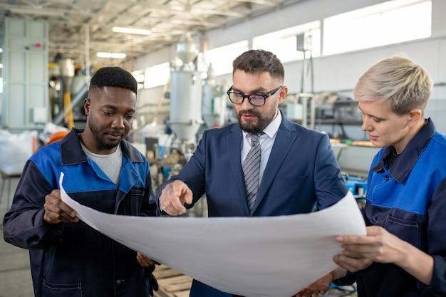 Industriemanager mit tablet, der mit arbeiter spricht und produzierte metallteile im fabrikladen untersucht