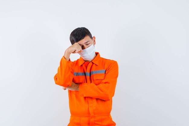 Industriemann, der auge reibt, während er in uniform, maske weint und traurig aussieht. vorderansicht.