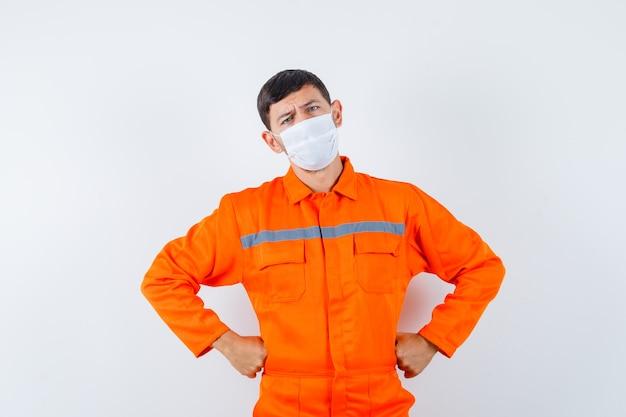 Industriemann, der hände auf taille in uniform, maske und nachdenklich aussehend hält. vorderansicht.