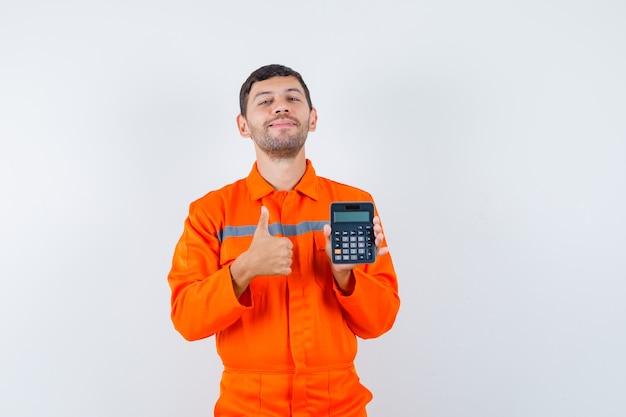 Industriemann, der taschenrechner hält, daumen oben in uniform zeigt und fröhlich aussieht. vorderansicht.
