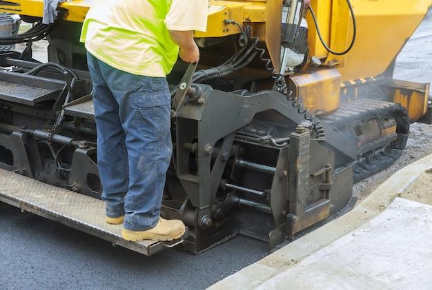 Industriemaschinen, die mit asphal industrial arbeiten und frischen asphalt verlegen