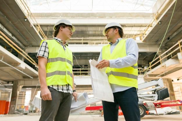 Industrieporträt von zwei männern, die auf der baustelle arbeiten. bau-, entwicklungs-, industrie- und personalkonzept