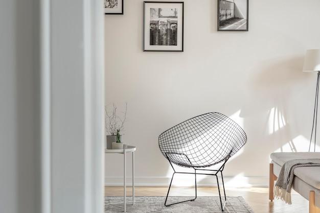 Industriestuhl mitten im schwarz-weißen interieur mit fotos an der wand