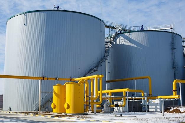 Industrietanks aus metall im freien. technologisches gebäude mit pipelines in der industrieanlage an der wand. ausrüstung und geräte bei der gasgesellschaft. gasleitungssystem mit ventil.
