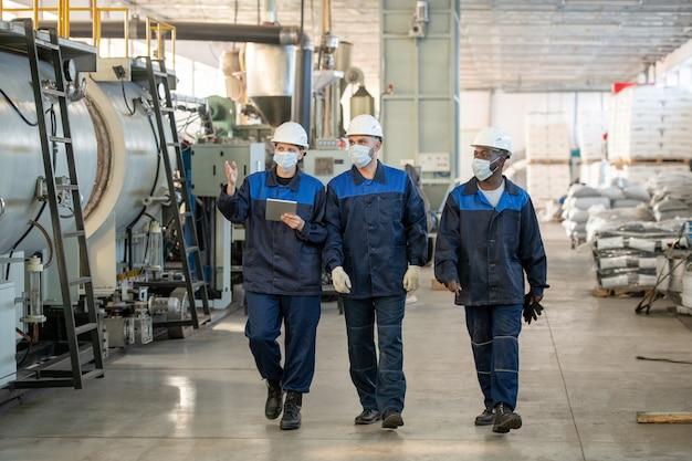 Industrietechnologe in formeller kleidung mit tablet, während er mit kollegen in der werkstatt über technische skizzen diskutiert