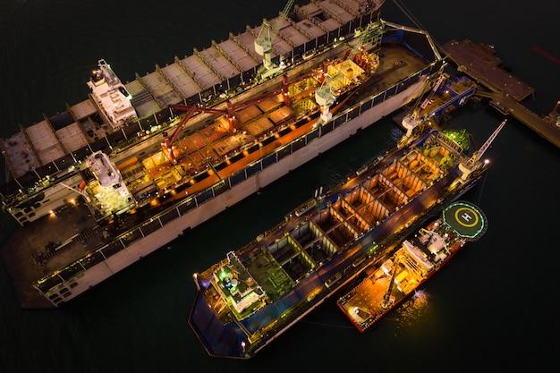 Industriewerft und reparatur großer schiffe in der seevogelperspektive nachts