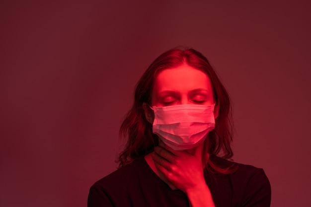 Infizierte junge frau in gesichtsmaske hält die augen geschlossen und fühlt schmerzen im hals, dunkelroter lichteffekt