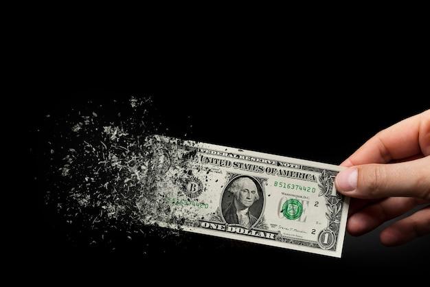 Inflation, dollar-hyperinflation mit schwarzem hintergrund. ein dollarschein wird in die hand eines mannes auf schwarzem hintergrund gesprüht. das konzept der abnehmenden kaufkraft, inflation.