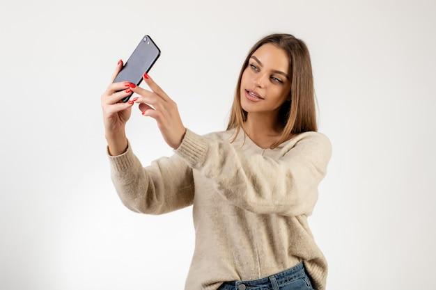 Influencer bloggerfrau, welche die vordere kamera des telefons getrennt über weiß betrachtet