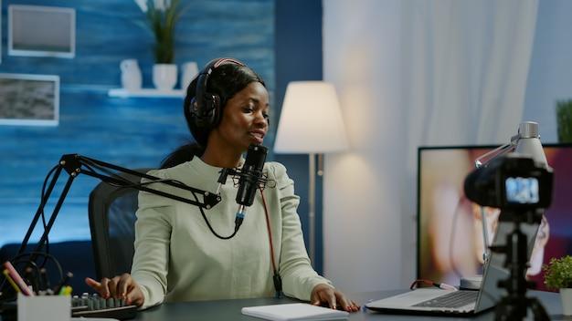 Influencer, der online-internetinhalte für web-abonnenten mit videokamera im home-podcast-studio während des livestreamings erstellt. on-air-online-produktionssendung, die live-inhalte streamt
