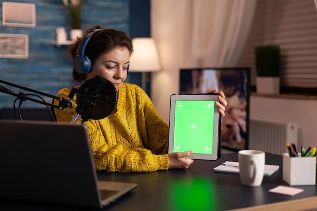 Influencer hält tablet mit greenscreen-display und nimmt neue podcast-serien für das publikum auf