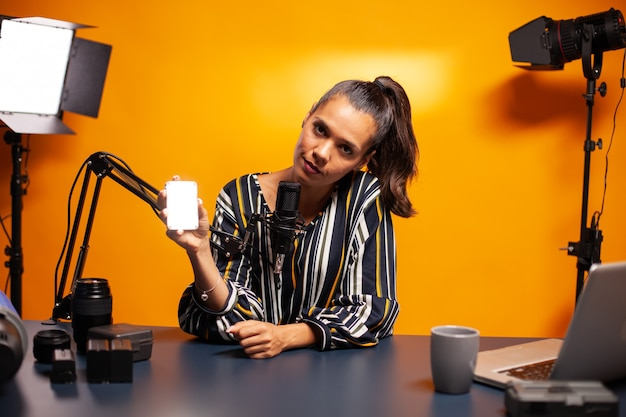Influencer präsentiert ein mini-led-licht für den professionellen einsatz während der aufnahme von vlog