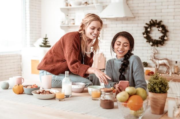 Informationen auf dem smartphone. blondes mädchen mit breitem lächeln, das freund über die situation fragt, die auf smartphone präsentiert wird, während sie zusammen frühstücken