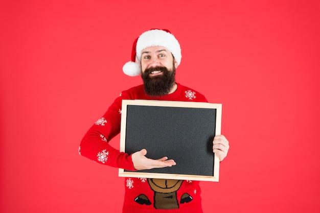 Informationen vom weihnachtsmann. bärtiger mann hält leere tafel. santa point an der informationstafel. informationen zu silvesterfeiern. weihnachtsfeier. werbeinformationen, kopienraum.
