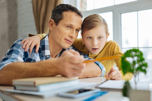 Informative lektion. angenehmer junger mann und sein jugendlicher sohn verbinden sich im büro des vaters, während der mann dem jungen über den nutzen von bäumen für die umwelt erzählt