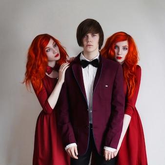Informeller typ mit langen haaren in jacke und zwei zwillingen mit langen roten locken im roten kleid mit fliege am hals