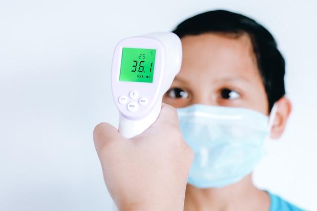 Infrarot-thermometer in einer hand, die die temperatur des asiatischen kleinen jungen mit der chirurgischen schutzmaske im gesicht misst