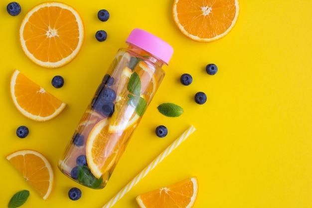 Infundiertes oder entgiftendes wasser mit orange und blaubeere in der flasche auf der gelben oberfläche.