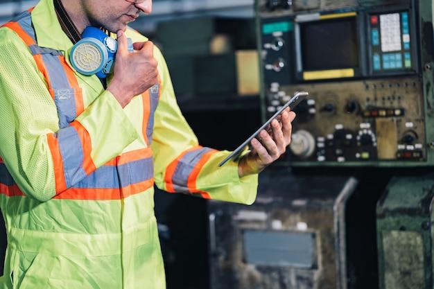 Ingenieur / arbeiter mann kaukasier in schützender sicherheitsoveralluniform mit gelbem helm