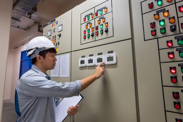 Ingenieur arbeitet und überprüft die elektrische energieverteilung der schaltanlage im umspannwerkraum des kraftwerks