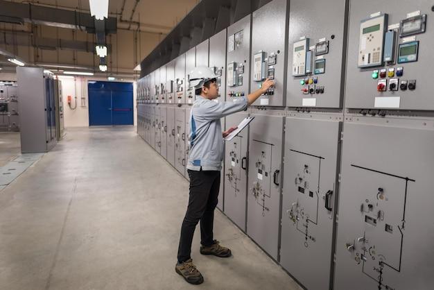 Ingenieur arbeitet und überprüft die elektrische energieverteilung der schaltanlage im umspannwerkraum