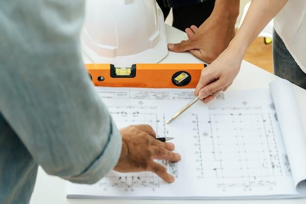 Ingenieur, architekt, bauarbeiterteam, das auf zeichnungsentwurf auf schreibtisch am arbeitsplatz im besprechungsraumbüro auf der baustelle, auftragnehmer, teamarbeit, baukonzept arbeitet und zeigt