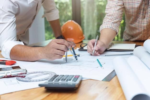 Ingenieur-architekten und immobilienmakler-büroteam, das mit plänen arbeitet