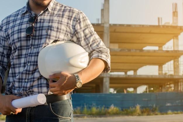 Ingenieur auf dem fachmann, der einen sturzhelm steht in der vorderen baustelle hält.