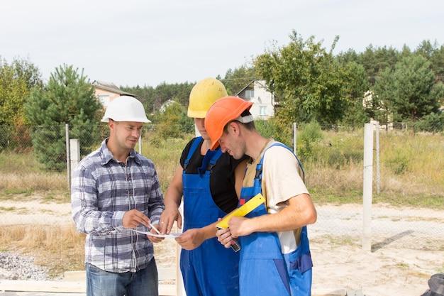 Ingenieur auf einer baustelle bespricht spezifikationen mit zwei arbeitern in overalls und schutzhelmen, die sich um ein dokument gruppieren