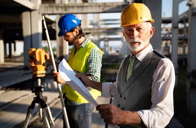 Ingenieur, auftragnehmer, architekt, investor teamwork. gruppe von bauleuten, die arbeiten sprechen und planen, blaupause halten