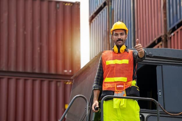 Ingenieur-bartmann, der mit einem gelben helm steht, um das laden zu kontrollieren und die qualität von containern vom frachtschiff für den import und export in der werft oder im hafen zu überprüfen