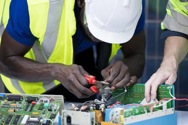 Ingenieur bei der reparatur von schalttafeln mit sonnenkollektoren hintergrund, konzept teamwork oder schulung von erneuerbaren.
