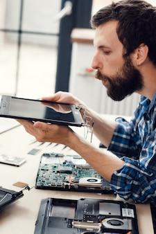 Ingenieur bläst staub vom digitalen bildschirm ab