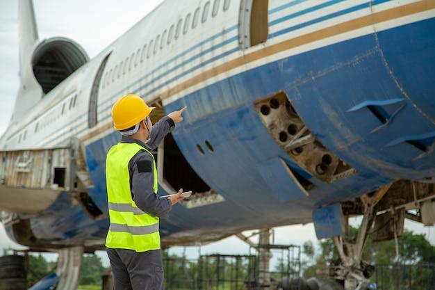 Ingenieur, der altes flugzeug für wartung ein flugzeug betrachtet, führen reparaturen durch.