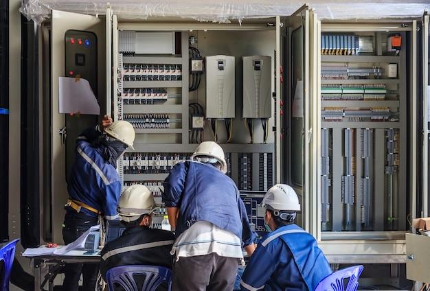 Ingenieur, der an überprüfungs- und wartungsausrüstung an der verdrahtung auf plc-kabinett arbeitet