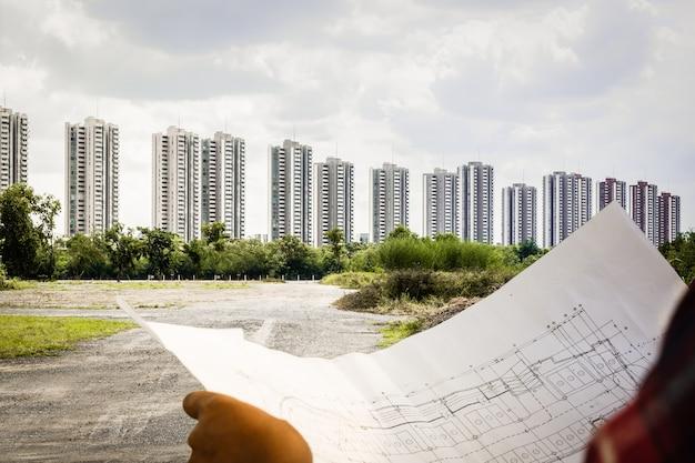 Ingenieur, der architekten mit planbaustellen-projektgebäude schaut und plant
