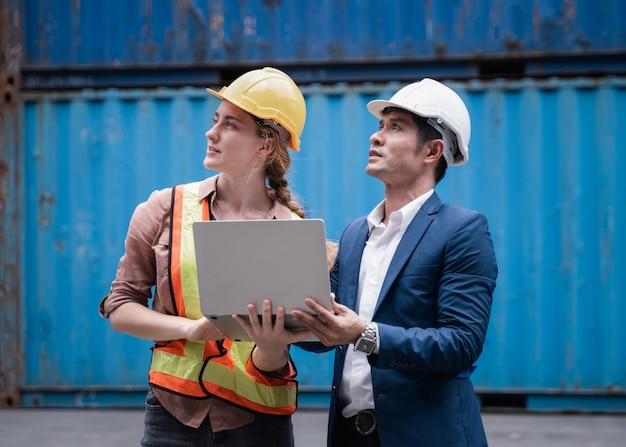 Ingenieur, der auf dem baucontainerhof, dem industriecontainerhof für den import und export für unternehmen arbeitet, vorarbeiter, der das industriecontainerfrachtschiff in der industriezone kontrolliert