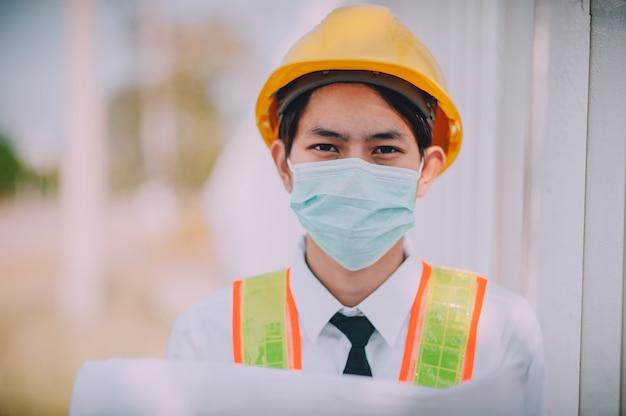 Ingenieur, der blaupause hält, tragen medizinische gesichtsmaskenarbeit auf der baustelle