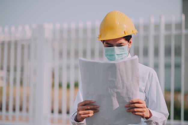Ingenieur, der blaupausen-baustellenhintergrund hält
