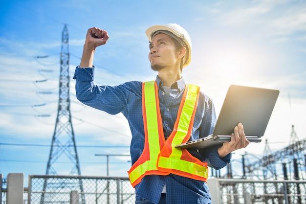 Ingenieur, der computernotizbuch oder laptop und ein kraftwerk mit dem industrietechnologiekonzept der elektrizitätsbehörde hält