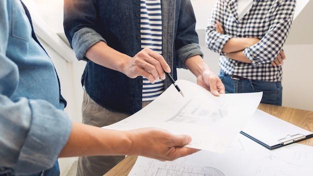 Ingenieur, der das treffen arbeitet an dem planprojekt architektonisch an der baustelle bespricht.