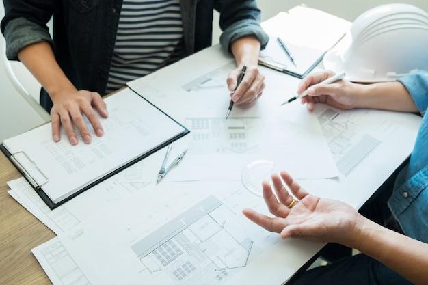 Ingenieur, der das treffen bespricht, das an planprojekt architektonisch an der baustelle arbeitet.