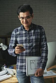 Ingenieur, der den plan hält und mitteilung auf smartphone simst