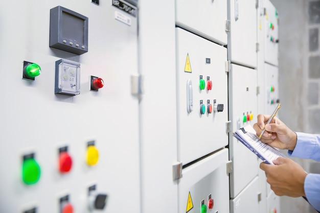 Ingenieur, der den starterknopf des luftbehandlungsgeräts am bedienfeldsystem überprüft.