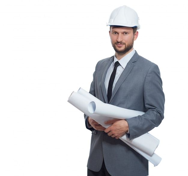 Ingenieur, der im sicherheitshut und in der grauen suite lächelt an der kamera trägt. isolieren sie auf weißem hintergrund.
