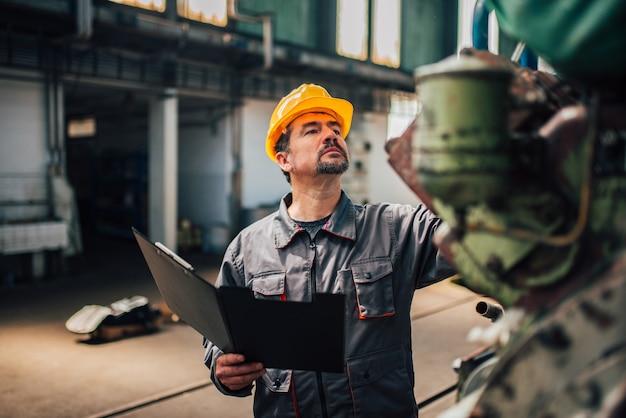 Ingenieur, der im werk eine qualitätsprüfung durchführt.