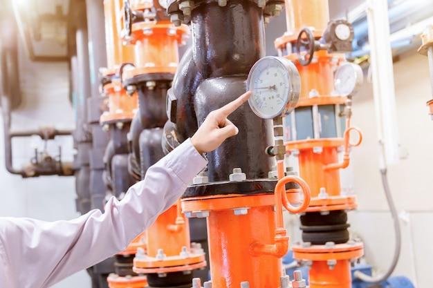 Ingenieur, der kondensator-wasserpumpe und druckanzeiger überprüft.