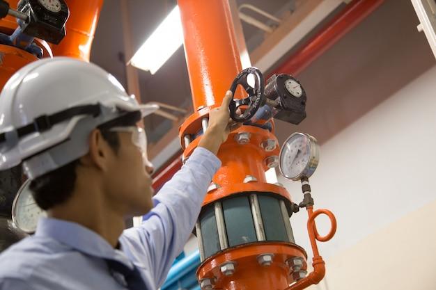 Ingenieur, der kondensator-wasserpumpe und -manometer überprüft