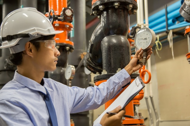 Ingenieur, der kondensatorwasserpumpe und -manometer, kühlerwasserpumpe mit manometer überprüft.
