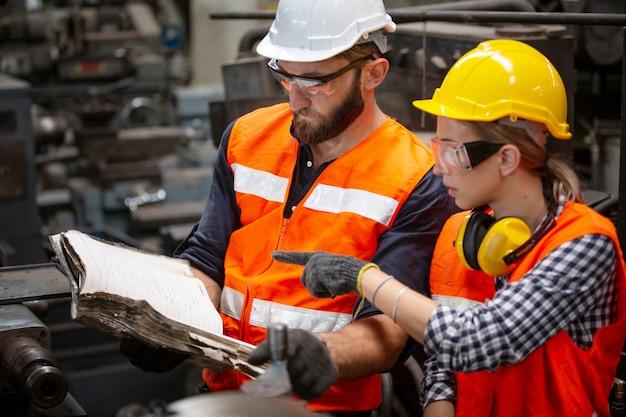 Ingenieur, der mit einer ingenieurin die bedienungsanleitung überprüft, während er eine cnc-maschine im werk bedient